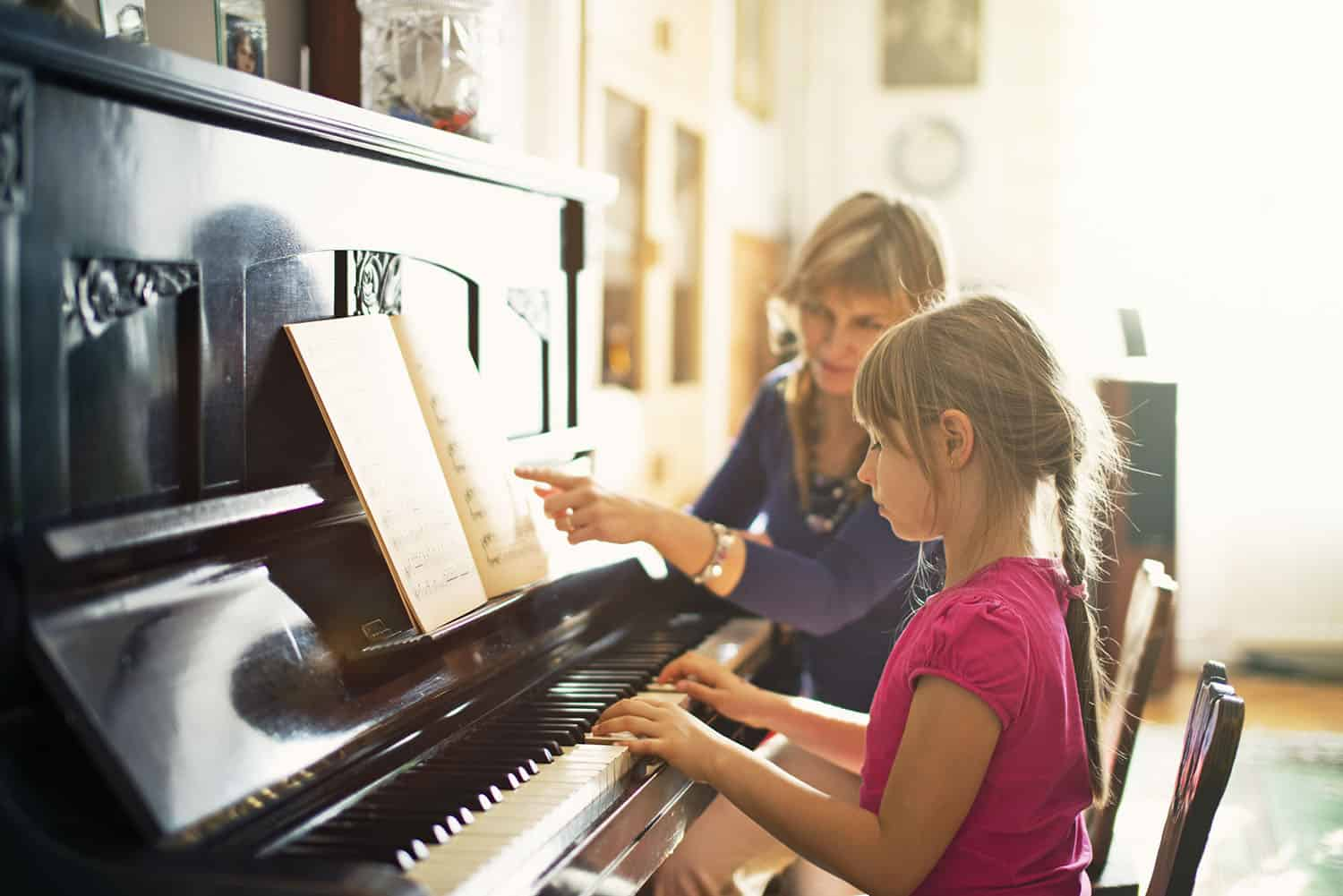 Mother teaching daughter to play piano. The girl is aged 7. Mother and girls are sitting by the old piano in a sunny room.